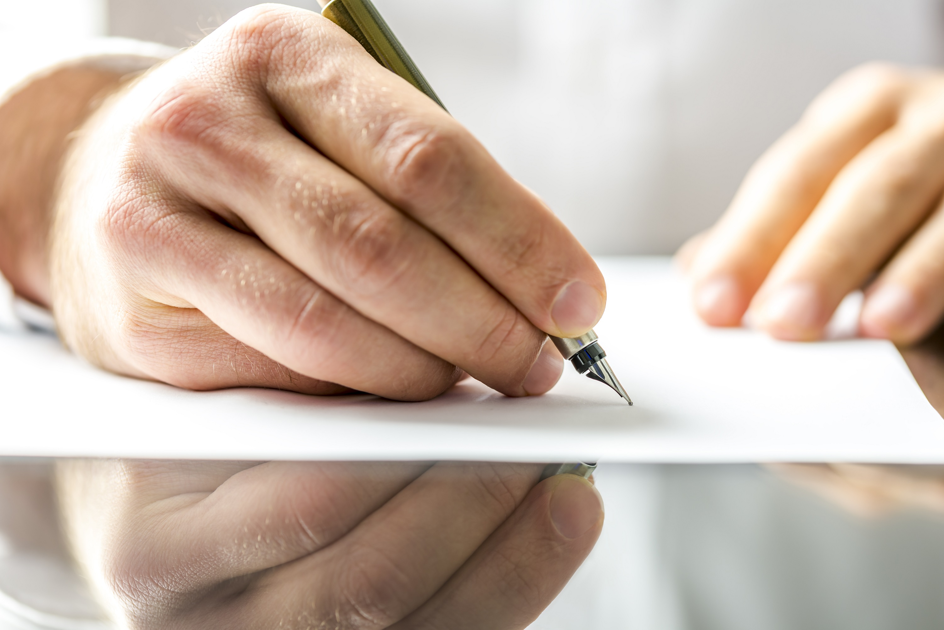 A man's hand writing on a piece of paper