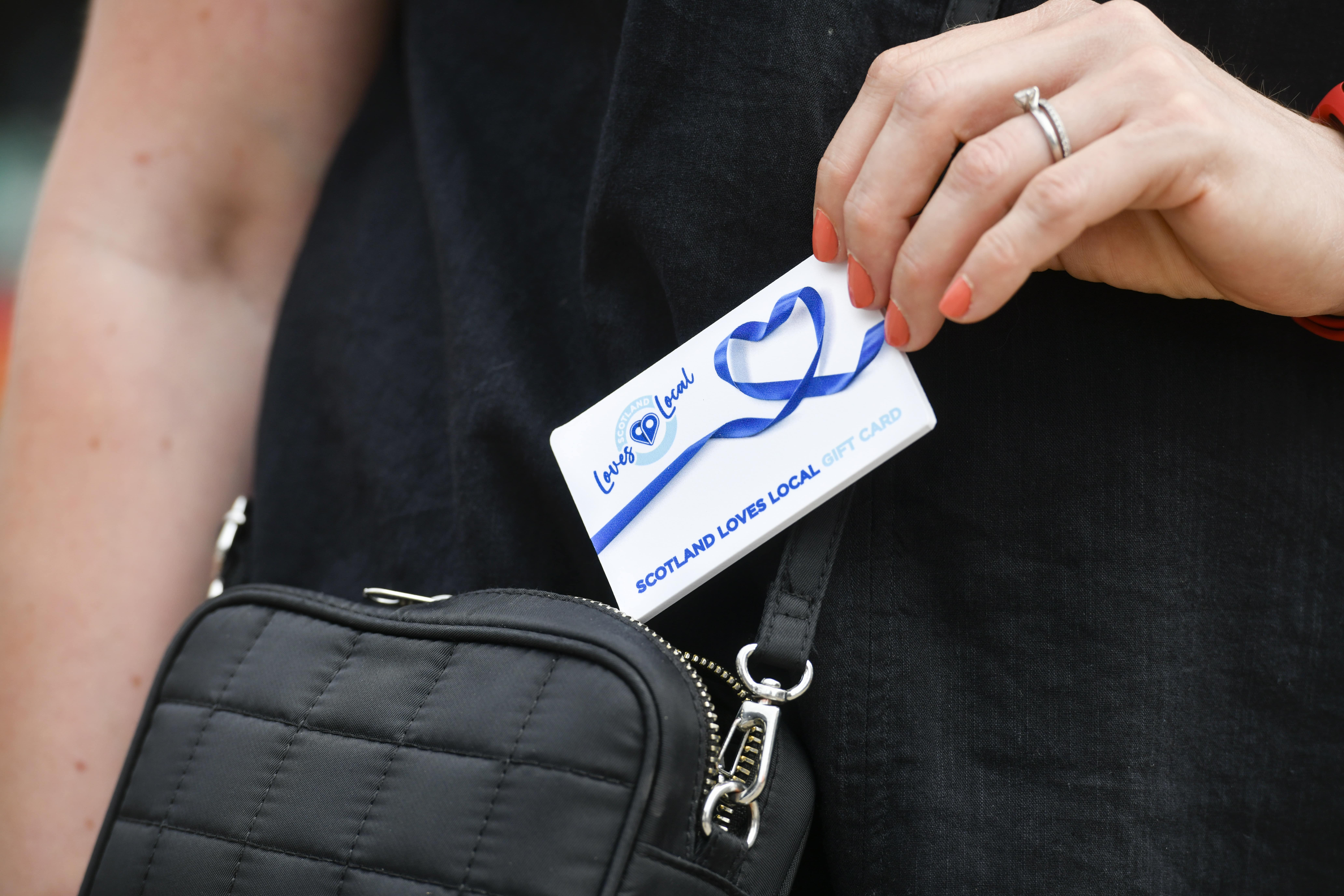A Scotland Loves Local gift card being taken out of a handbag